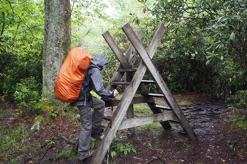 Backpacker crossing over cattle fence along the Appalachian Trail in the rain. Ladder. photo