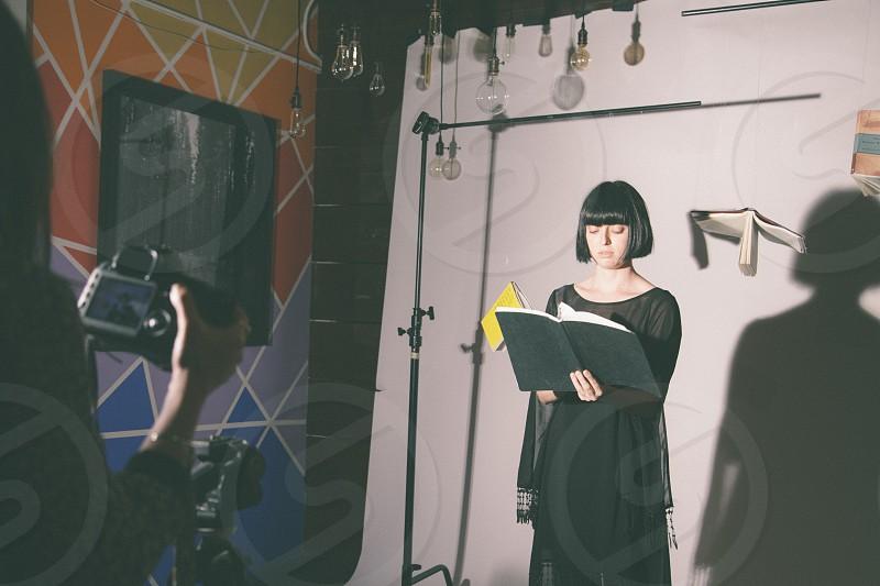 woman in black long sleeve dress holding black book photo