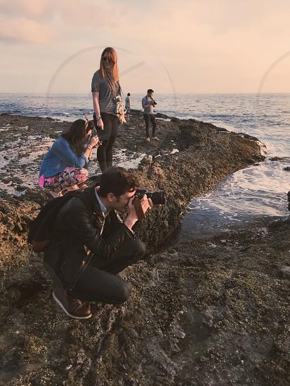 man in black jacket using dslr camera on brown rock beside 2 women during daytime photo
