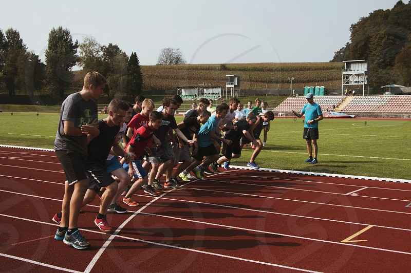 Poeple at a starting line on the running track. photo