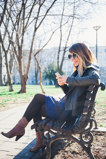 Young woman sitting on the bench in the park using smartphone photo