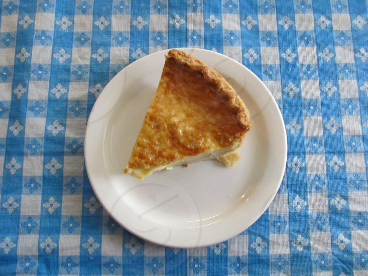 Slice of egg custard pie on white plate on blue and white checkered tablecloth photo