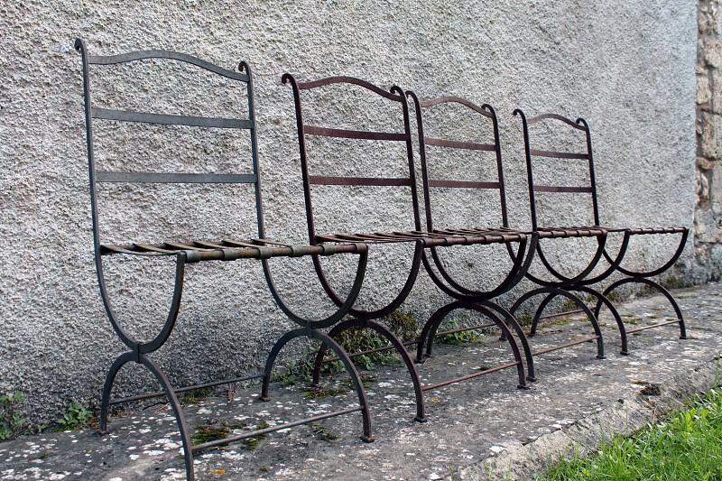 black metal chair near wall photo