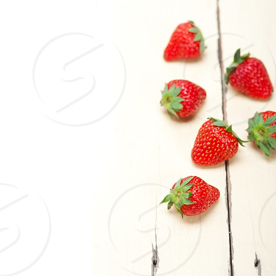 fresh organic strawberry over white rustic wood table photo