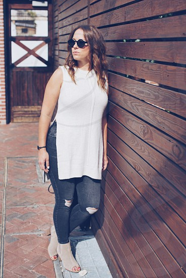 woman in white sleeveless crew neck side slip top gray denim distressed jeans and gray peep toe chunky heeled sandals with black framed sunglasses leaning in brown wooden plank wall photo