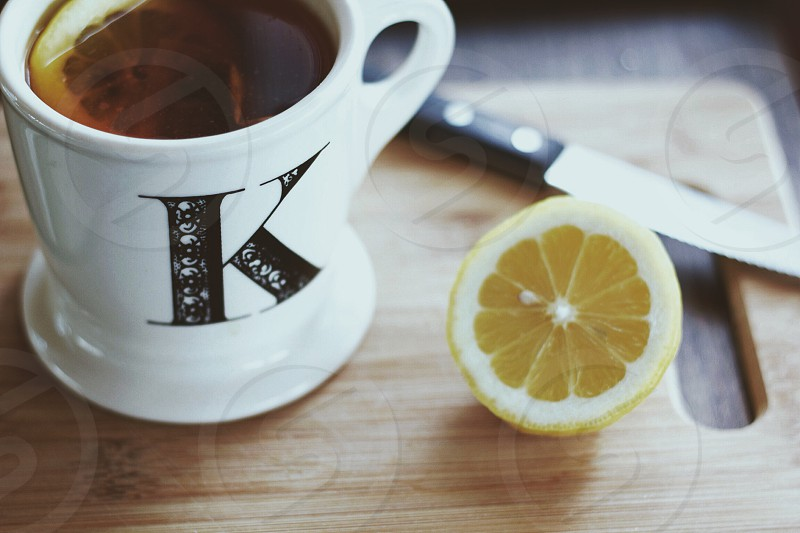 yellow sliced lemon with white ceramic coffee cup on brown wooden chopping board photo