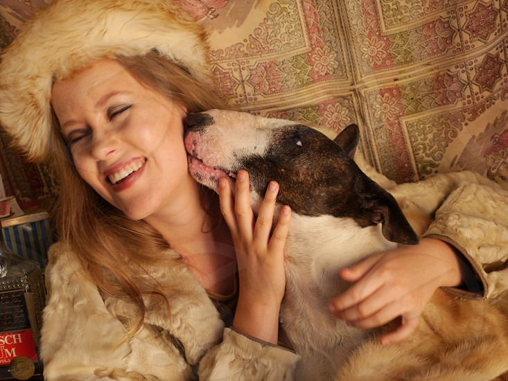 Cute pet dog licking girl owner fur coat Russian photo