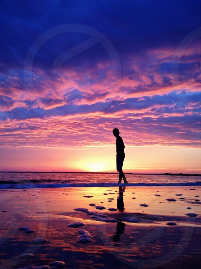 man standing in the seashore photo
