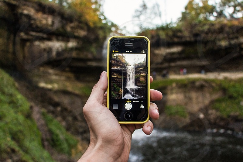 person capturing image of waterfalls using yellow iphone 5c during daytime photo