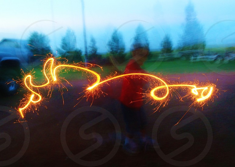 person doing a light painting using a sparkler photo