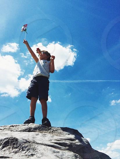boy wearing white sleeveless shirt and black shorts standing on rock monolith photo