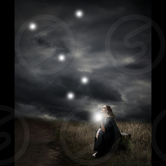 woman sitting while looking in star during nighttime photo