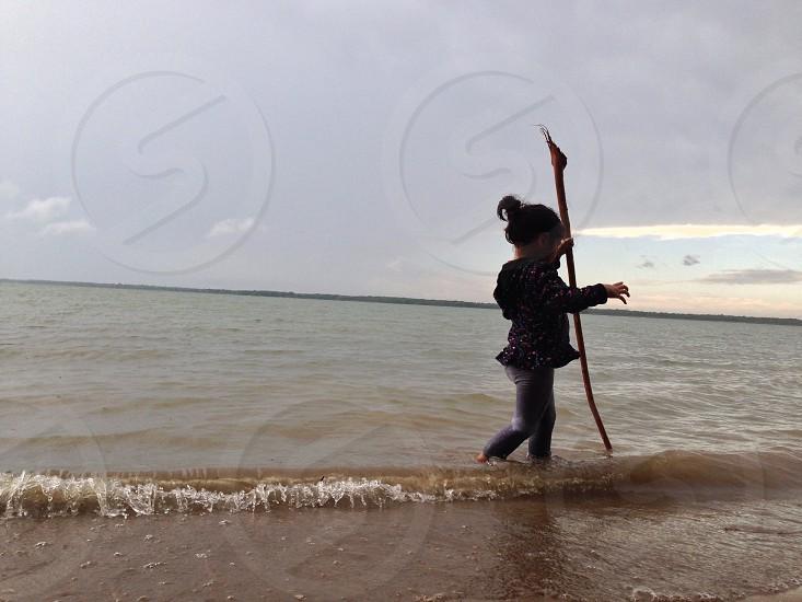 child standing near body of water photo