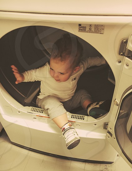 baby sitting inside white front load clothes dryer photo
