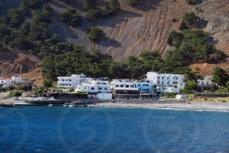 panoramic view of Crete (Greece) mountains of Libyan Sea side. driving with a boat along from Samaria gorge towards Loutro village. In background village Agia Roumeli photo