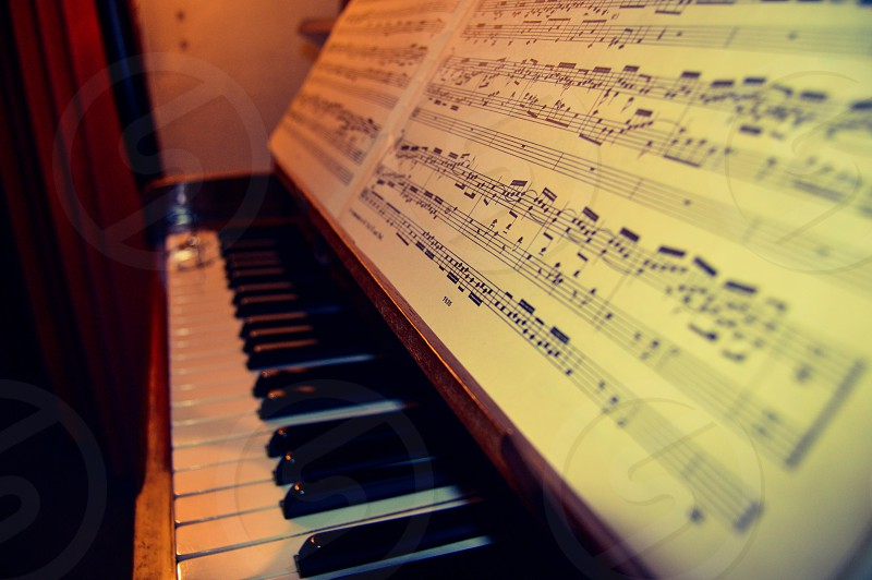 close-up photo of brown wooden framed piano with 2-page musical sheet placed on head board photo