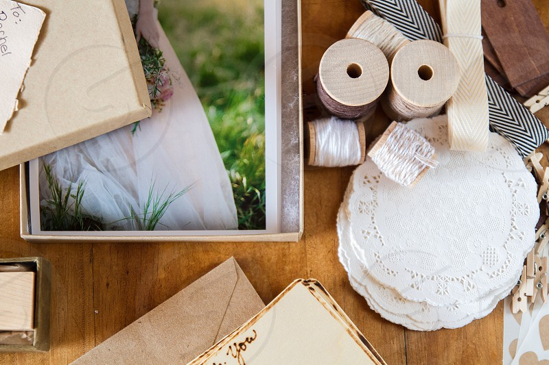 An assortment or spools of thread tags doilies and cards sit next to a package of wedding photo prints. photo