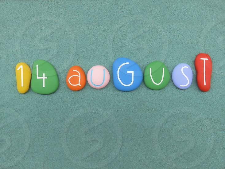 14 August calendar date composed with multi colored stones over green sand                          photo