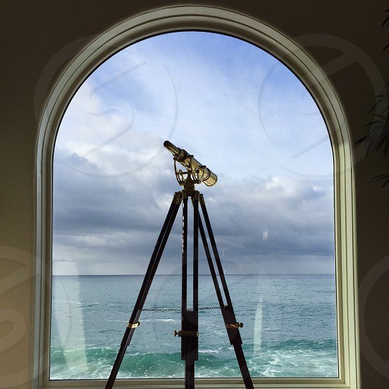 black telescope with tripod in front of glass window and sea water under gray sky during daytime photo