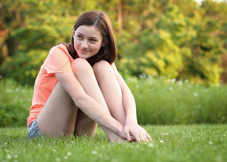 A teenage girl smiles while sitting on some lush green grass in front of a meadow. photo
