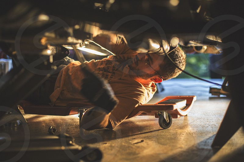 man fixing vehicle underneath photo