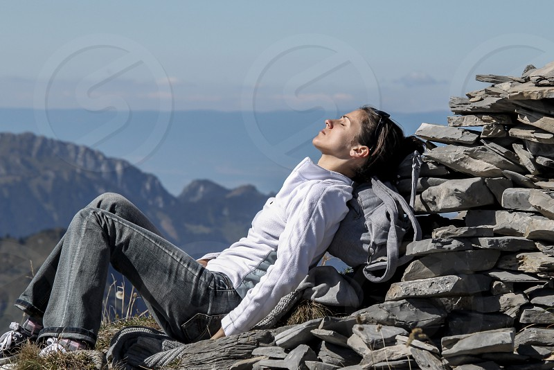 woman in white shirt lying on rock formation photo