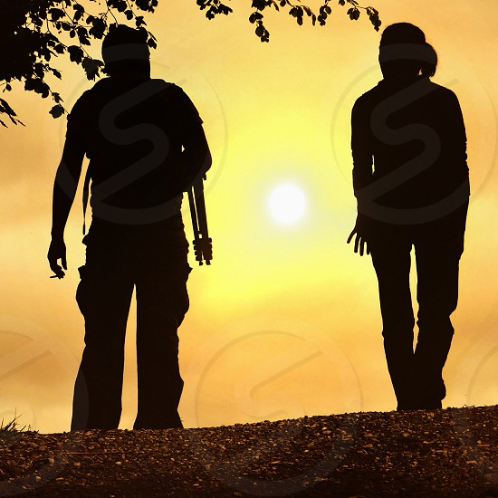 two silhouettes watching sun rise photo
