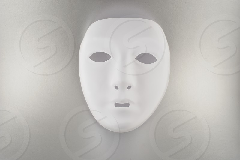 Plastic white face mask. White mask on a silver background. Plastic human mask photo