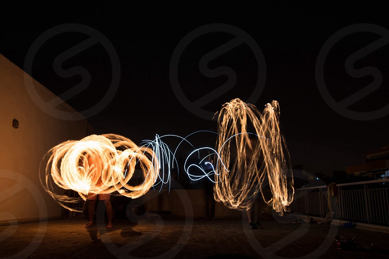 people swirling lights standing on a patio photo