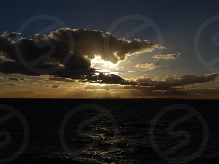 sunset sun rays clouds sea photo