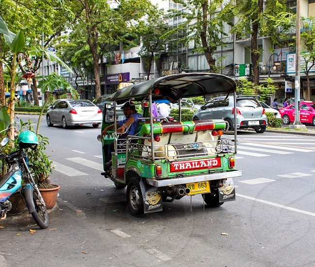 man riding on green and pink auto rickshaw photo