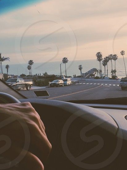 person riding car by gray rolled asphalt road  under white clouds photo