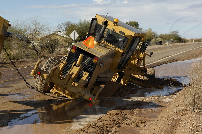 A road grader that got stuck in the mud along an Arizona road. photo