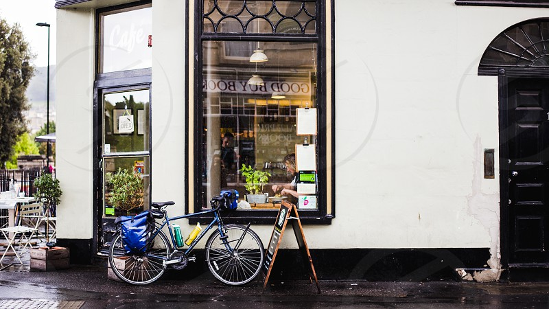 A stationary bike in front of a small cafe in Bath England likely left by the owner inside. photo