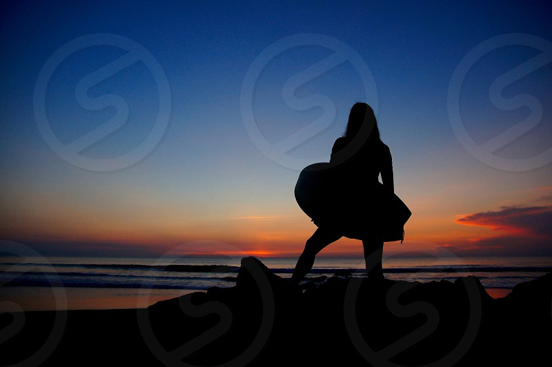 Silhouette surfer woman female surfer girl morning sunrise sunrise silhouette artistic abstract.  photo