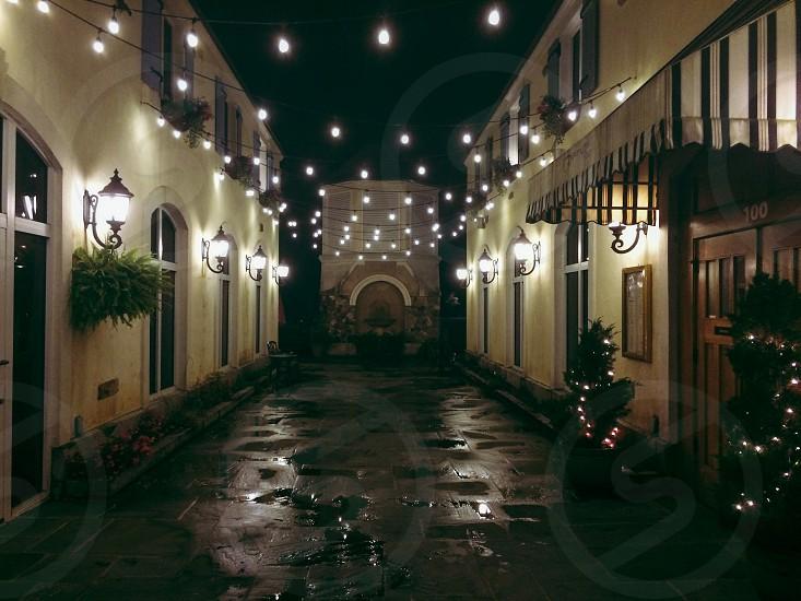 walkway between 2 buildings hanging lights photo