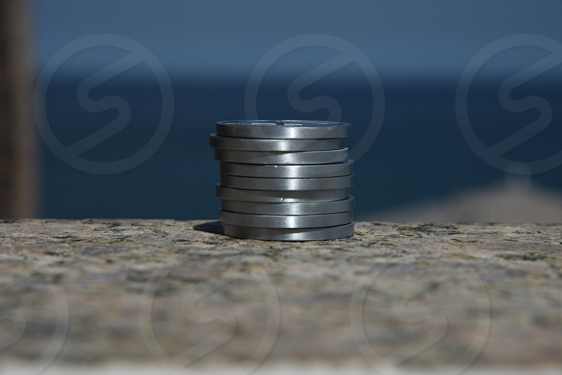 A stack of silver coins outside with the ocean in the background photo