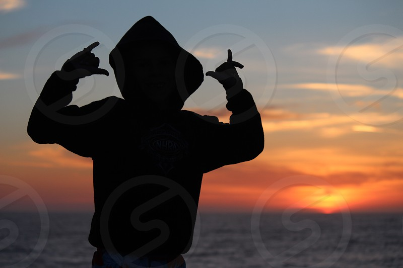 silhouette of person wearing hooded jacket during sunset photo