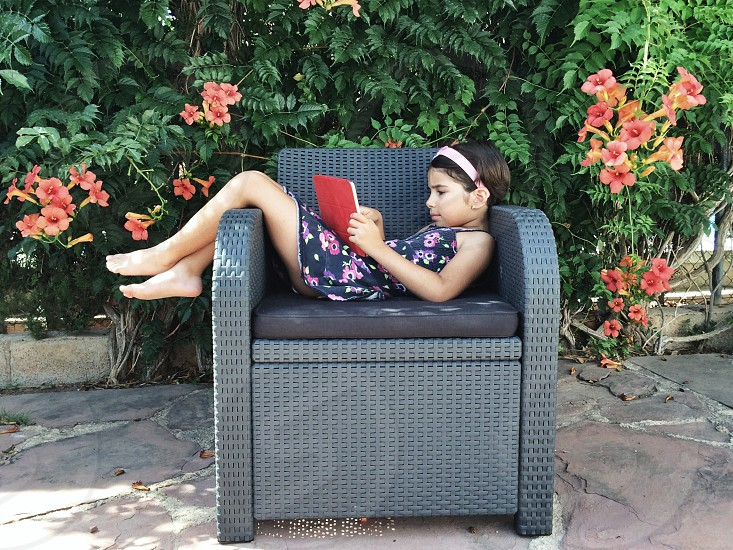 Girl playing with tablet on a summer afternoon. Outdoors.  photo