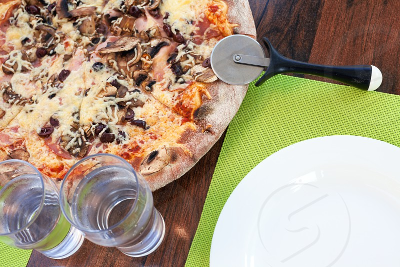 Lunch time Greek Pizza on table and accessories.  photo
