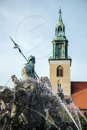 View of the Neptune  Fountain with Marienkirche in the background in Berlin photo