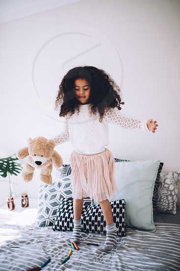 Little african girl jumping on bed with teddy bear photo