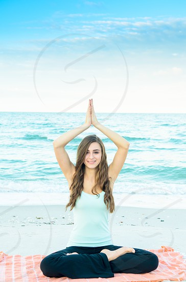A young woman on the beach doing yoga. photo