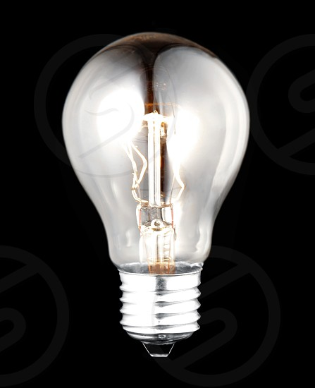 electric bulb lightened isolated on black background photo