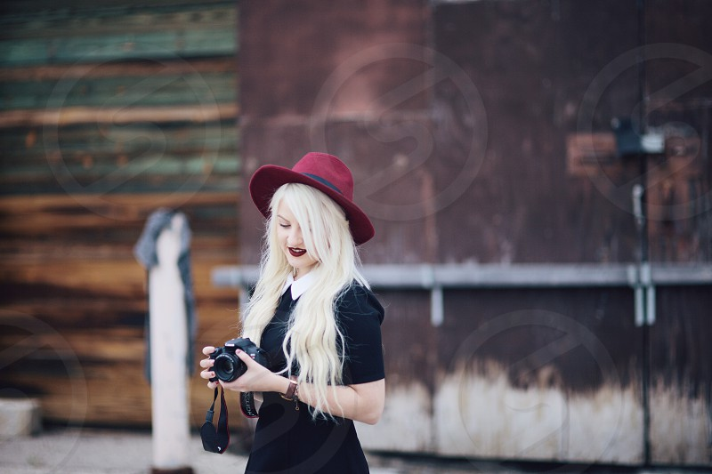 woman in black dress holding slr camera photo
