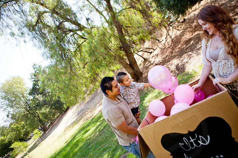 Baby Girl announcement Beautiful young Pregnant Mom Hispanic dad and toddler son photo