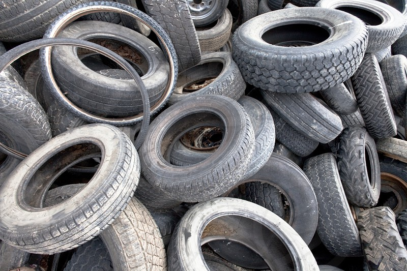 Frame filling background of a pile of used old tires and wheels for rubber recycling photo
