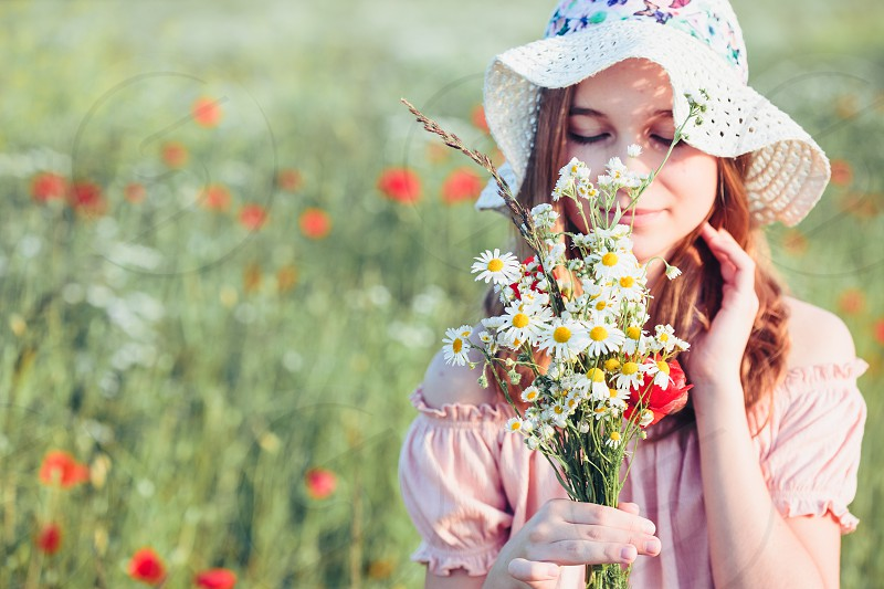 Beautieful young girl in the field of wild flowers. Teenage girl picking the spring flowers in the meadow holding bouquet of flowers. She wearing hat and summer clothes. Spending time close to nature photo