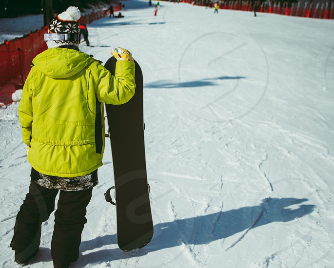 A snowboarder onlooking skiers coming down the slope. photo