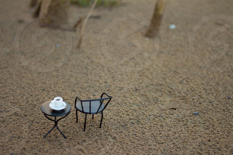 black patio table and armchair miniature set on top of brown sand photo